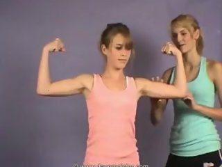 2 young girls comparing their muscles